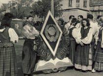 Kauno universiteto liaudies ansamblio nariai ruošiasi dalyvauti Gegužės 1-osios parade, 1950 m. Prie stilizuoto ženklo stovi studentas R. Tamutis, 1951 m. tapęs šokių grupės vadovu.