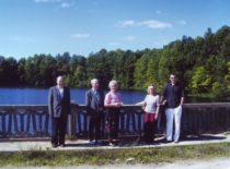 Ragulskiai ant Varduvos tilto, 2005 m. Užnugaryje V. Ragulskienės tėviškė Dapšių kaimas (Mažeikių raj.) Iš kairės: sūnus Liutauras, Kazimieras, Vyda, marti Jūratė, sūnus Minvydas, 2005 m.